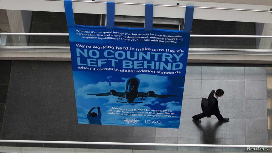 FILE - A delegate walks past a banner during a break at the International Civil Aviation Organization's (ICAO) global safety meeting in Montreal, Feb. 4, 2015.