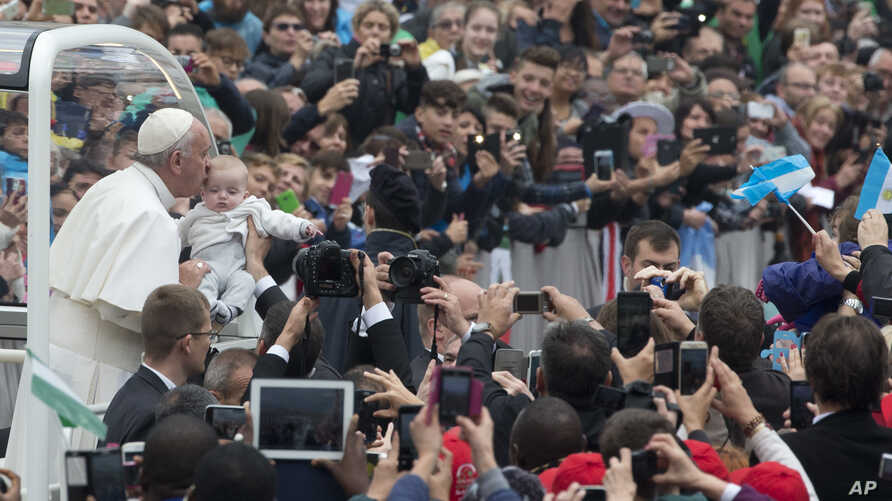 Pope Francis kisses a baby as he arrives for his weekly general audience in St. Peter's Square at the Vatican, Wednesday, Oct. 28, 2015.