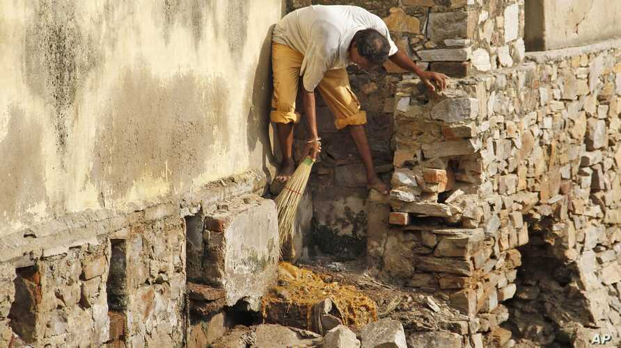 FILE - A low-caste sweeper cleans excreta flowing out of a public toilet at Ajmer, India.