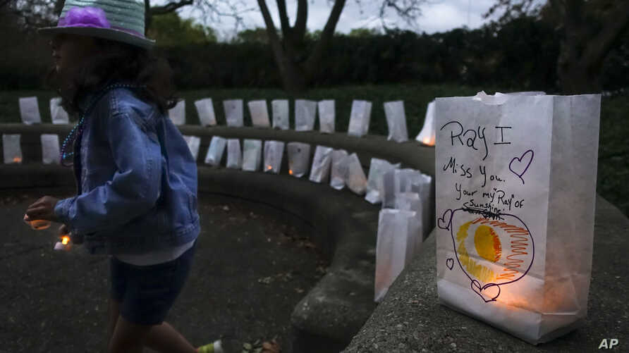 FILE - A young volunteer helps set up lights in paper bags decorated with messages for loved ones during an Out of the Darkness Walk event organized by the Cincinnati Chapter of the American Foundation for Suicide Prevention, Oct. 15, 2017, in Cincin