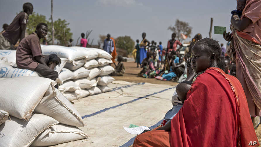 People wait to receive food at a World Vision food distribution site in Malualkuel in the Northern Bahr el Ghazal region of South Sudan, April 5, 2017.