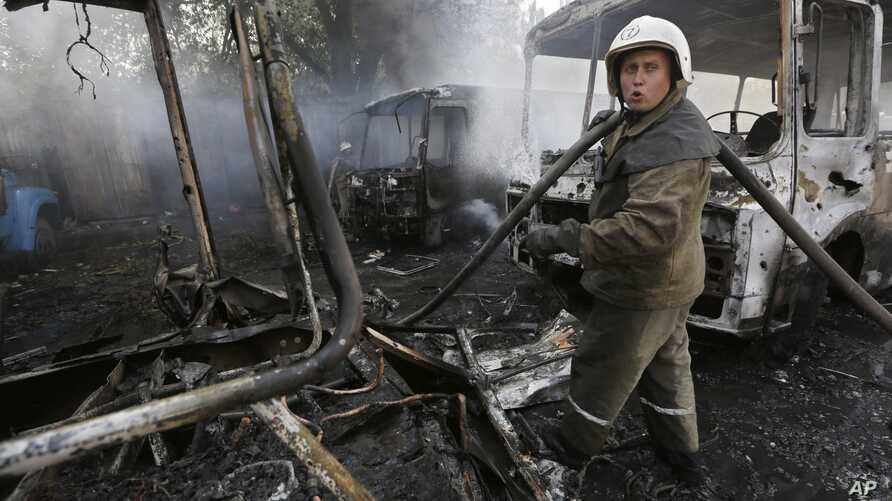 Ukrainian fire fighters put out the fire at the destroyed buses after shelling in Donetsk, eastern Ukraine, Aug. 10, 2014.