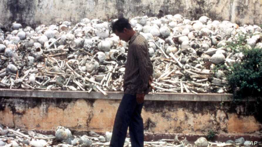 FILE - A Cambodian man is seen at one of the Killing Fields where vast numbers of people were killed by the Khmer Rouge regime.