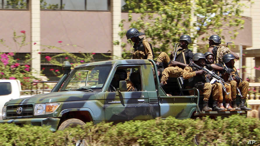 Troops ride in a vehicle near the French Embassy in central Ouagadougou, Burkina Faso, March 2, 2018, after an attack on the facility and two others.
