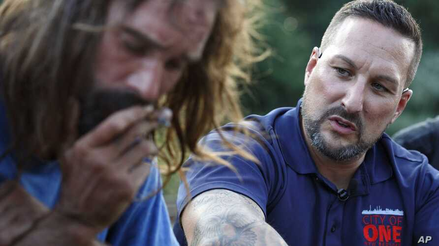 FILE - Pastor Jamie Casey, right, speaks with Brian Peets at a homeless camp in New Bedford, Mass., Aug. 10, 2018.