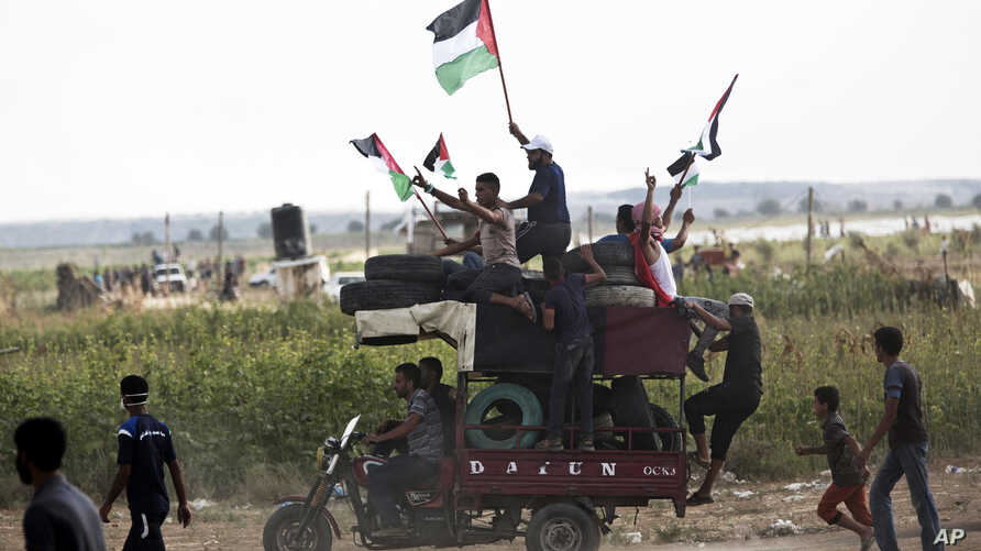 Men wave national flags while riding a motorcycle tax loaded with tires to be burned during a protest at the Gaza Strip's border with Israel, Aug. 3, 2018. Gaza's Hamas rulers led several thousand Palestinians in a protest along the frontier with Isr