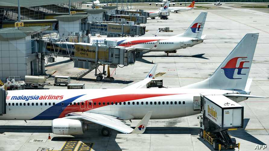 Catering service trucks (R) load inflight supplies onto Malaysia Airlines aircraft at Kuala Lumpur Intenational Airport (KLIA) in Sepang, March 25, 2014.
