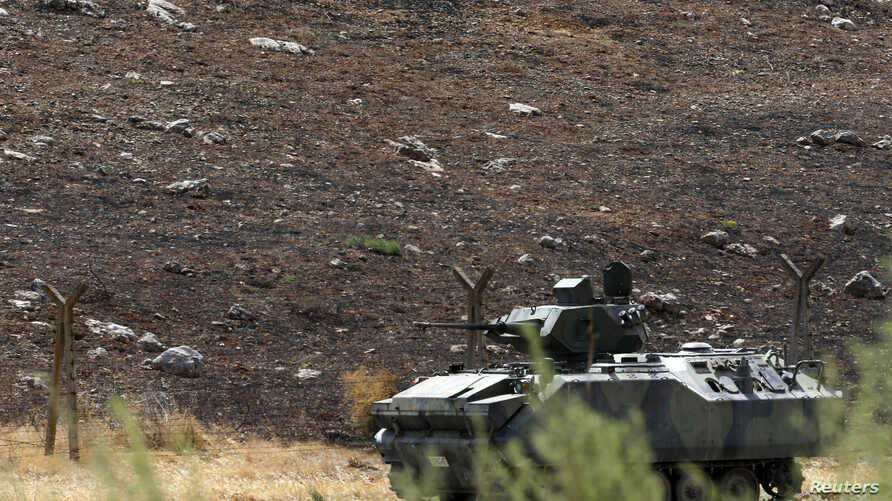A Turkish military armoured vehicle patrols on the border line near Turkish Cilvegozu border gate, located opposite the Syrian commercial crossing point Bab al-Hawa in Reyhanli, Hatay province, Sep. 17, 2013.