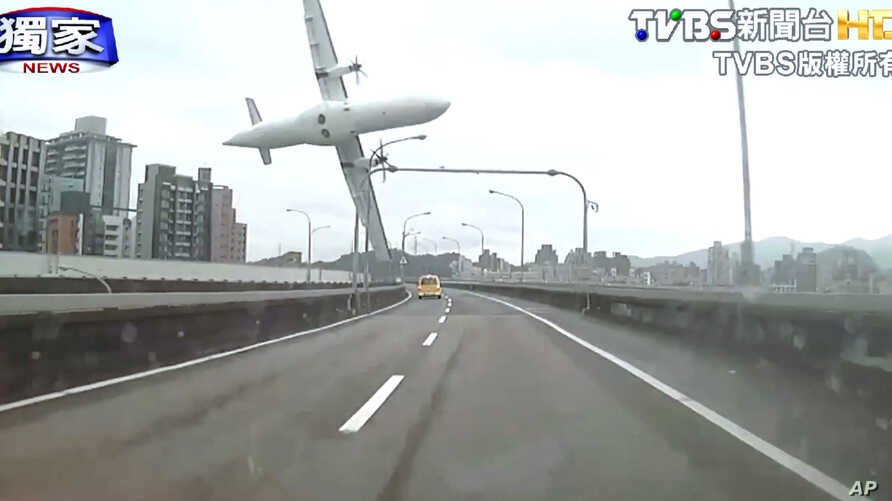 This image taken from video provided by TVBS shows a commercial airplane moments before it clipped an elevated roadway and careened into a river in Taipei, Taiwan, Feb. 4, 2015.