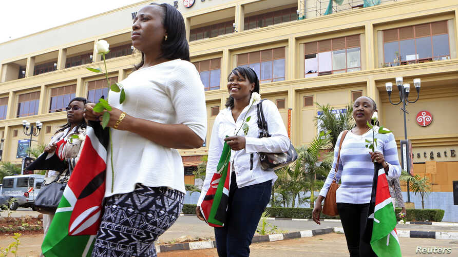 Survivors and relatives of victims carry Kenyan national flags as they attend the first anniversary memorial service of the Westgate shopping mall terrorist attack in Kenya's capital Nairobi, Sept. 21, 2014.