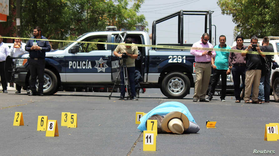 Evidence identifiers are placed next to the body of journalist Javier Valdez at a crime scene in Culiacan, Mexico, May 15, 2017.
