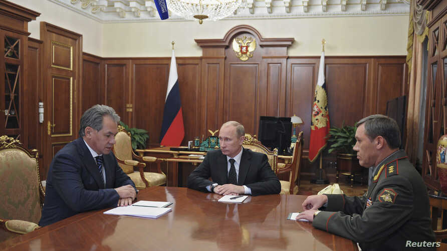 Russian President Vladimir Putin (C) speaks with newly appointed armed forces Chief-of-Staff Valery Gerasimov (R) and Defence Minister Sergei Shoigu during their meeting in Moscow's Kremlin November 9, 2012.