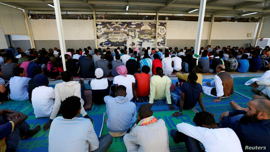 FILE - Migrants attend prayers at a detention center in Tripoli, Libya, June 15, 2018.