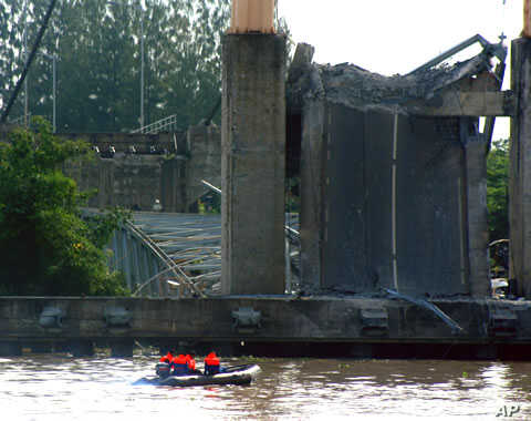 Rescuers search for victims as the ruins of the Kutai Kartanegara bridge is seen in the background in Tenggarong, East Kalimantan, Indonesia, November 27, 2011.