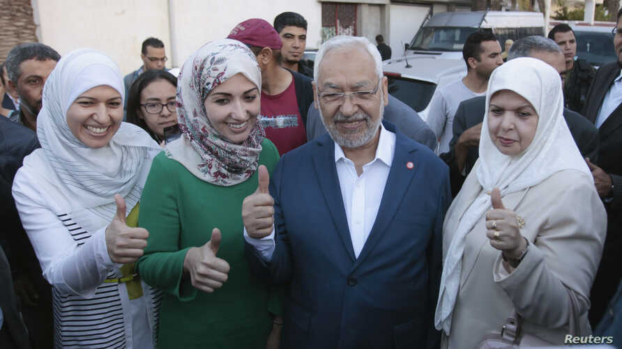 Rached Ghannouchi (C), leader of the Tunisian Islamist party Ennahda, gestures with his wife and two daughters Yousra (L) and Soumaya (2nd L) at a polling station during an election in Tunisia October 26, 2014.Tunisians voted on Sunday in parliamenta