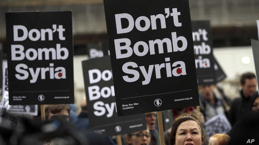 Protesters take part in a small demonstration organized by the Stop the War Coalition against possible military intervention or bombing by western allies in Syria, in London, April 13, 2018.