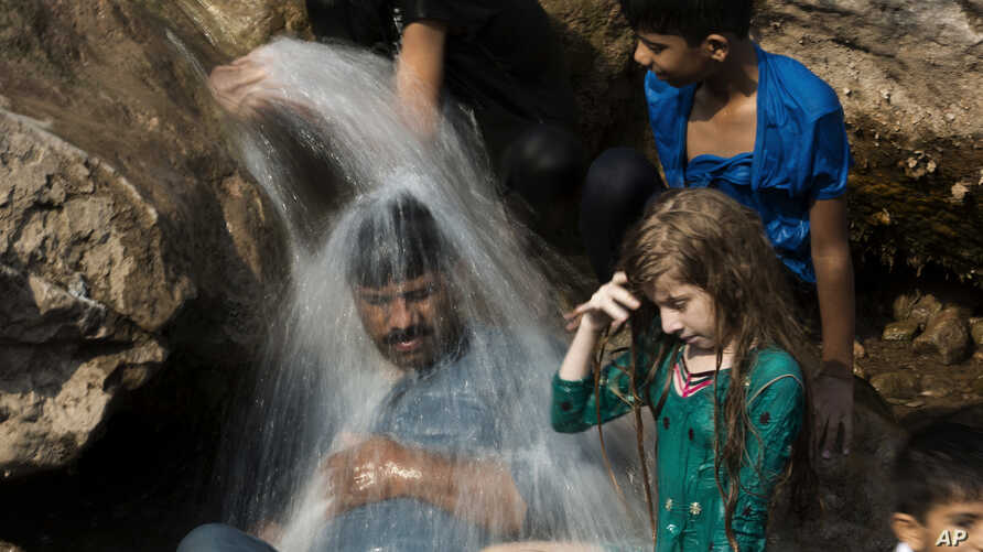 FILE - A family cools off in a stream during a heat wave, in Islamabad, Pakistan, May 30, 2017. The town of Turbat in southwestern Pakistan reported a temperature of 54 degrees Celsius in May.