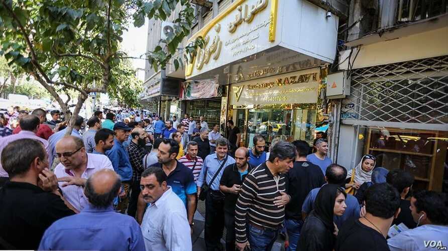Iranians line up outside a currency exchange shop in Tehran in this recent photo published by Iran's Fars news agency.