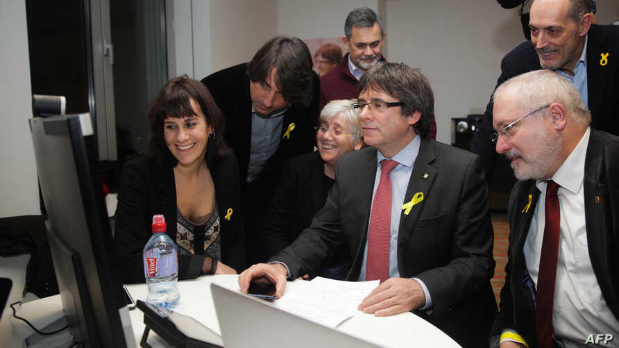 FILE - Axed Catalan president Carles Puigdemont flanked by deposed government's members looks on a computer at the results of the Catalonia's regional elections, at the Square - Brussels Meeting Centre in Brussels on Dec. 21, 2017.
