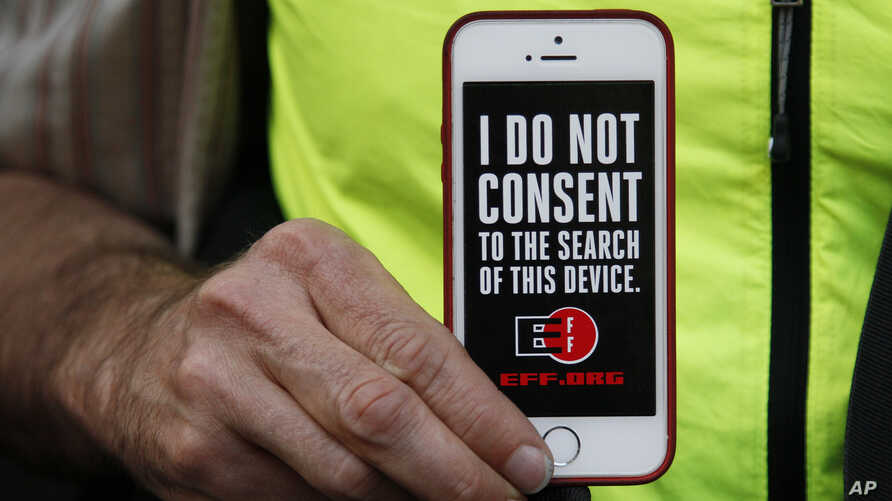 FILE - A man holds up his iPhone during a rally in support of data privacy outside the Apple Store in San Francisco, Feb. 23, 2016.