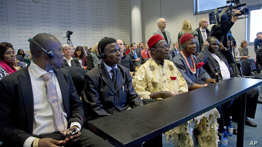 Plaintiffs Alali Efanga, Friday Alfrad Akpan, Chief Fidelis A. Oguru, Eric Dooh, and lawyer Chima Williams wait for the start of a court case against Shell, in The Hague, October 11, 2012.