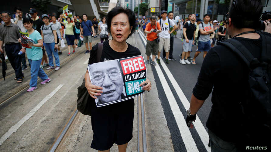 FILE - An activist holds a placard demanding the release of Chinese Nobel Peace Laureate Liu Xiaobo during a demonstration on the 20th anniversary of the territory's handover from Britain to Chinese rule, in Hong Kong, China, July 1, 2017.