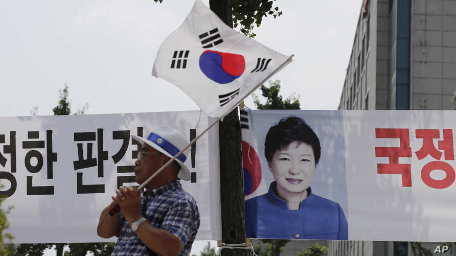 A supporter of former South Korean President Park Geun-hye waves a national flag near the Seoul Central District Court in Seoul, South Korea, July 20, 2018. A South Korean court has sentenced jailed former South Korean President Park Geun-hye to an a