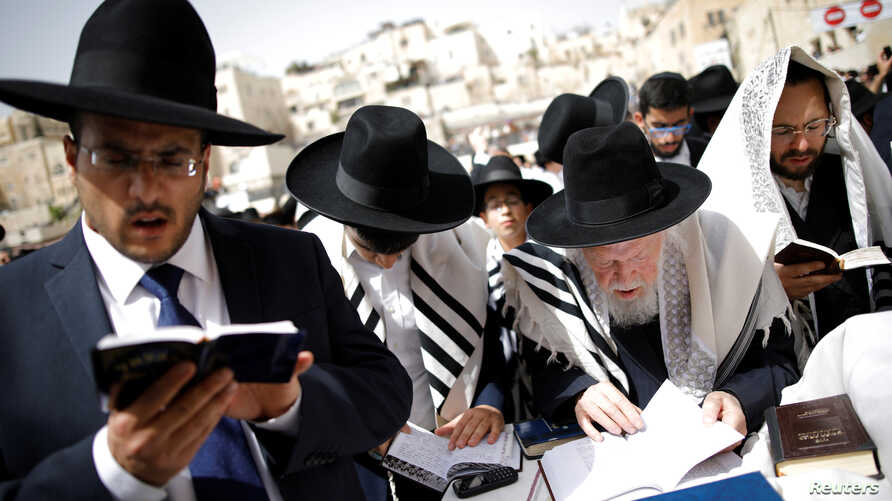 Ultra-Orthodox Jewish worshippers take part in the priestly blessing prayer on the holiday of Passover at the Western Wall in Jerusalem's Old City, April 13, 2017.
