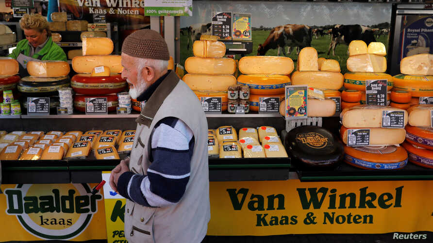 FILE - A man walks by a cheese stall at a market in The Hague, Netherlands.