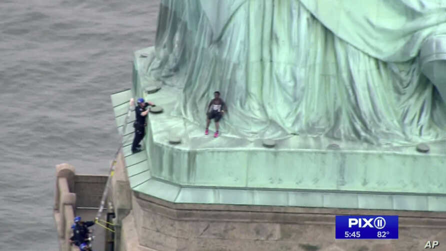 In this image made from video by WPIX, a person, center, leans against the robes of the Statue of Liberty on Liberty Island, as a police officer stands on a ledge nearby, talking the climber into descending, in New York, July 4, 2018.In this image ma...