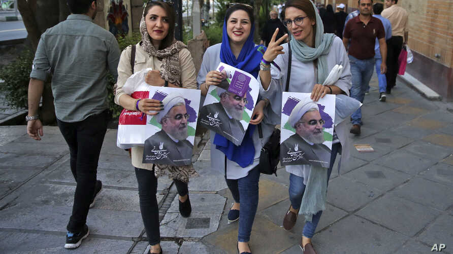 Supporters of Iranian President Hassan Rouhani hold posters with his image, May 17, 2017, during a street campaign ahead of Friday's presidential election in downtown Tehran, Iran.