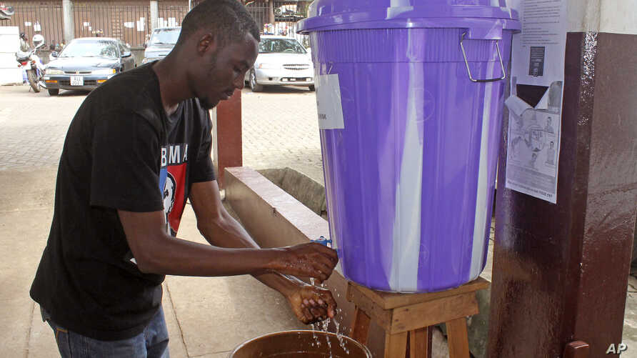 FILE - A man washes his hands with disinfectant to prevent Ebola infection before entering a hospital in the capital city of Freetown, Sierra Leone.