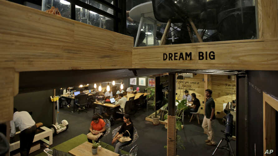 FILE - young Indian entrepreneurs and freelancers work inside Innov8, a lax co-working space in New Delhi, India.