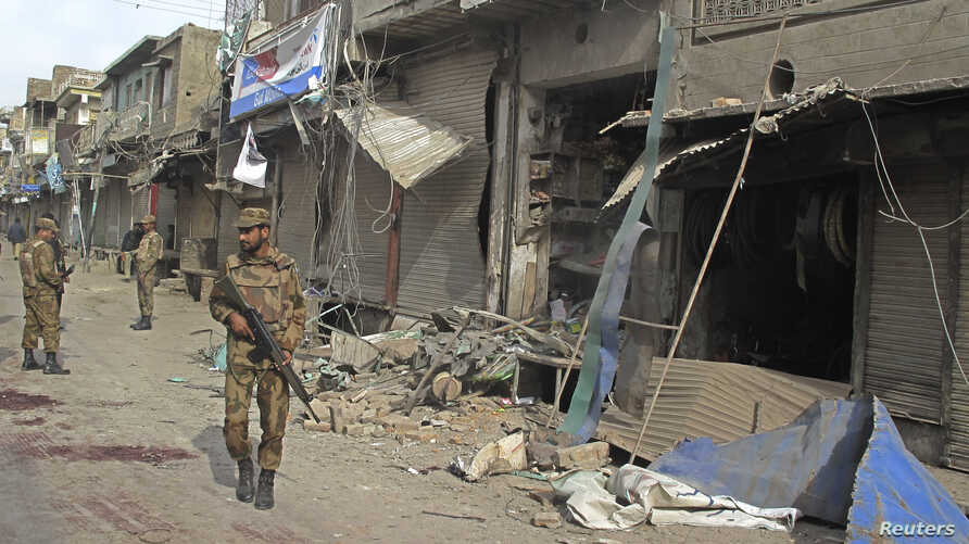 A security official walks in front of a damaged shop after a remote control bomb blast took place near a Shi'ite procession in Dera Ismail Khan in Pakistan's northwest, November 25, 2012.