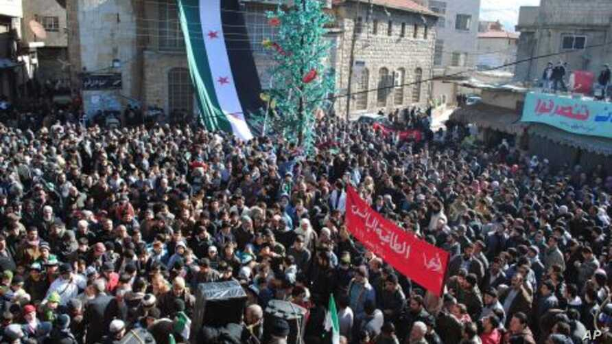 Anti-Syrian regime protesters gather at a square as they hold an Arabic banner, center, reading, 'hey, the miserable, the tyrant, what else,' during a demonstration at the mountain resort town of Zabadani, Syria, near the Lebanese border, January 20,