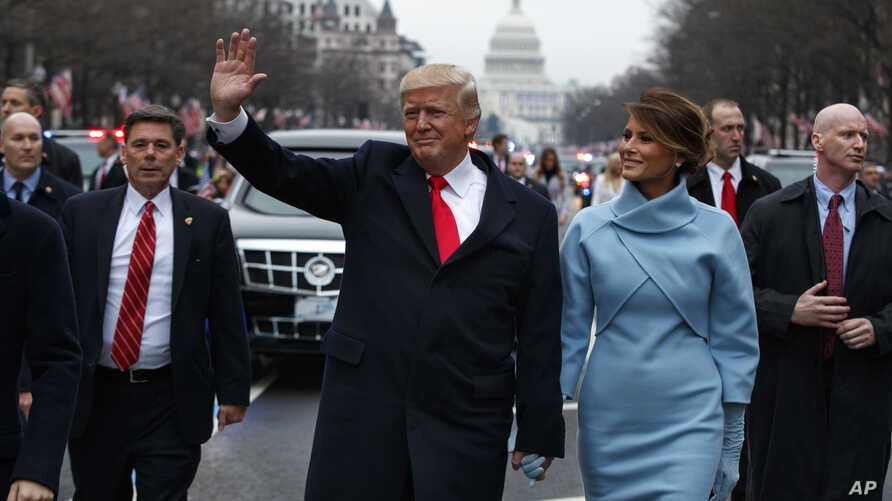 FILE - President Donald Trump and first lady Melania Trump walk along the inauguration day parade route on Pennsylvania Avenue after he was sworn in as the 45th President of the United States, Jan. 20, 2017, in Washington.