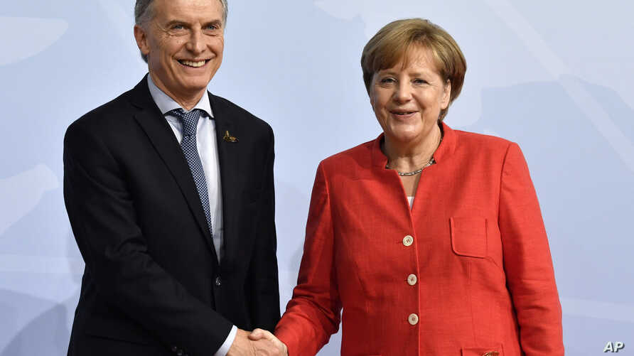 German Chancellor Angela Merkel greets Argentina's President Mauricio Macri at the start of the G-20 meeting,  July 7, 2017, in Hamburg, Germany. Argentina has ratified the Mercosur deal, and other trade deals, including with the European Union, are