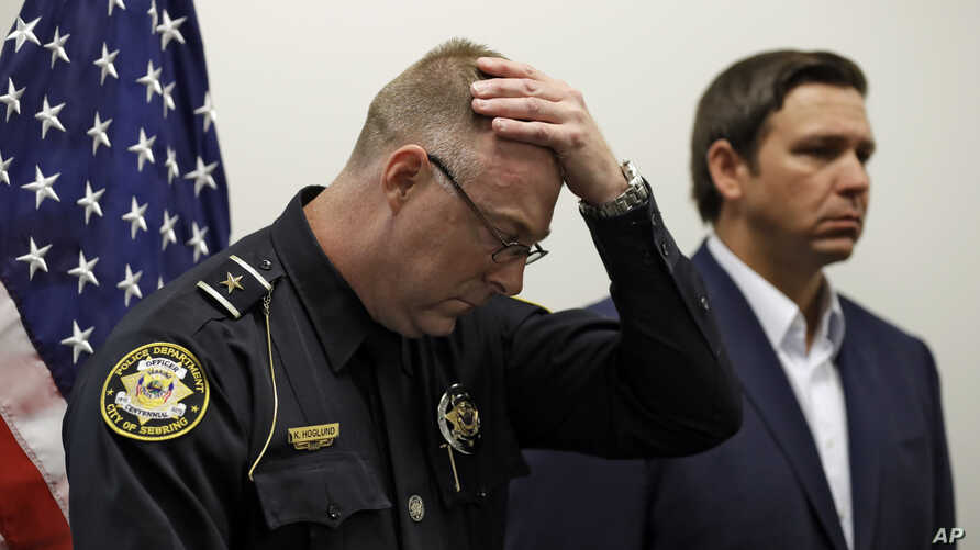 Sebring, Florida, police chief Karl Hoglund wipes his head as he listens to Florida Gov. Ron DeSantis speak during a news conference,  Jan. 23, 2019,  after authorities said five people were shot and killed at a SunTrust bank branch.