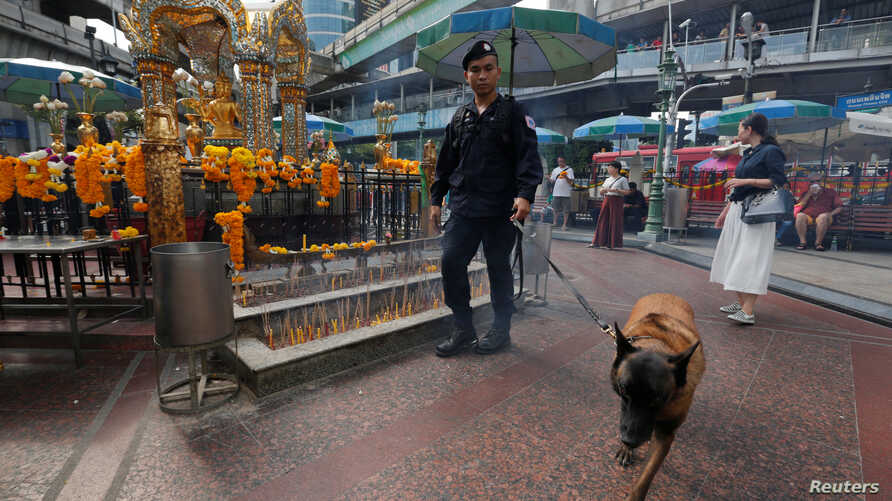 A Thai police officer and his dog inspect around the Erawan shrine during the first anniversary of the shrine's bombing in central Bangkok, Thailand, Aug. 17, 2016.