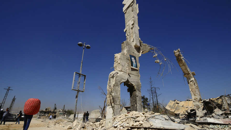 A picture of Syria's President Bashar al-Assad is displayed on a damaged structure at the entrance of al-Dukhaneya neighbourhood near Damascus,  October 7, 2014. REUTERS/Omar Sanadiki