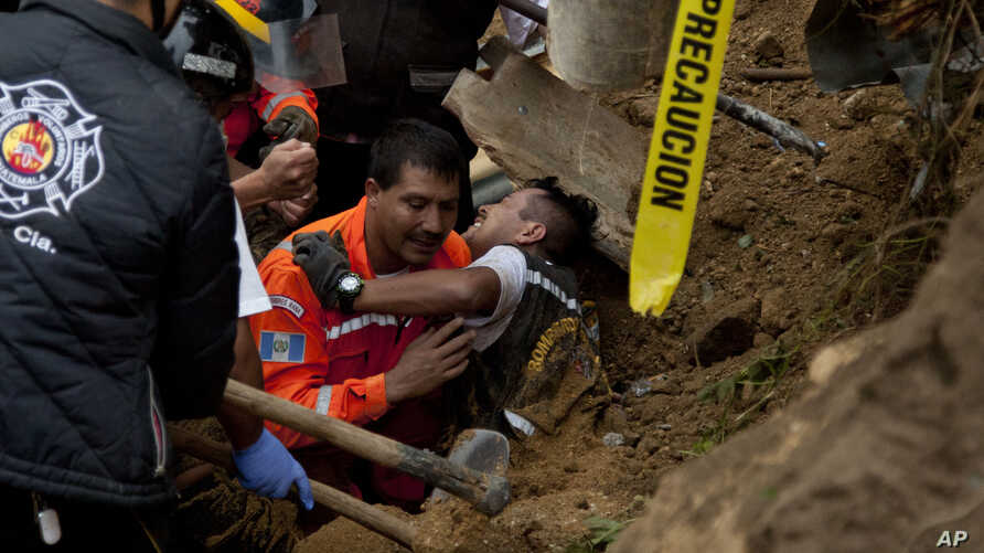 A fireman is rescued after he was trapped while working at the site of a landslide in Cambray, a neighborhood in the suburb of Santa Catarina Pinula, about 10 miles east of Guatemala City, Oct. 3, 2015.