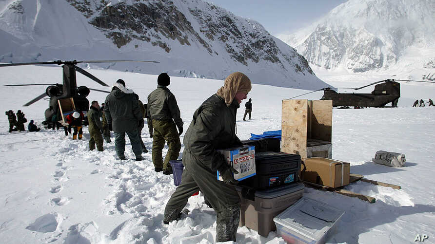FILE - In this April 15, 2002, file photo, members of the U.S. Army's High Altitude Rescue Team from Fort Wainwright Army Base near Fairbanks, Alaska, unload supplies from the team's CH-47 Chinook helicopters for the National Park Service's 7,000-foo