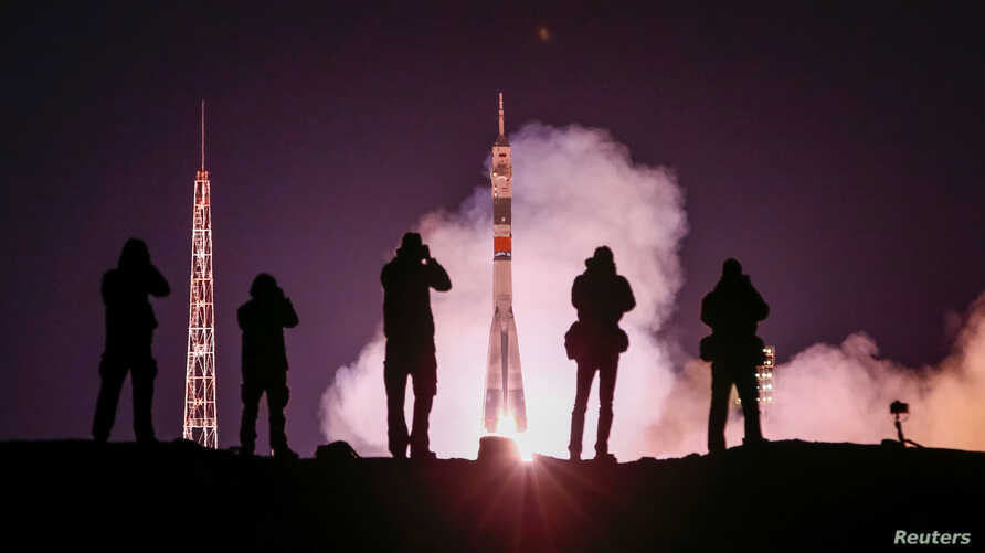 Photographers take pictures as the Soyuz MS-12 spacecraft carrying Aleksey Ovchinin of Russia, Nick Hague and Christina Koch of the U.S. blasts off to the International Space Station (ISS) from the launchpad at the Baikonur Cosmodrome, Kazakhstan, Ma