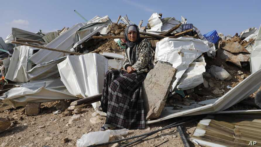 A Bedouin woman sit on demolished structure of a house in the Bedouin village of Umm al-Hiran, near the southern city of Beersheba, Israel Wednesday, Jan. 18, 2017.