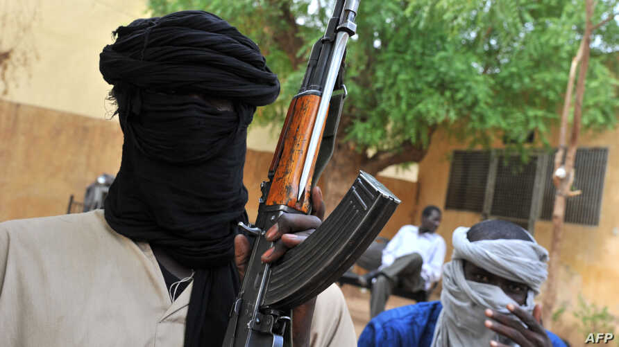 A picture taken on July 16, 2012 shows fighters of the Islamist group Movement for Oneness and Jihad in West Africa (MUJAO) sitting in the courtyard of the Islamist police station in Gao.