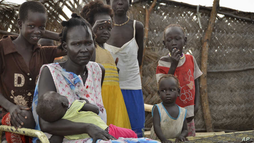 Yanut Ayuel, 2nd left, sits with her family at the displaced persons' camp where she lives in Abayok, South Sudan, Aug. 20, 2017.