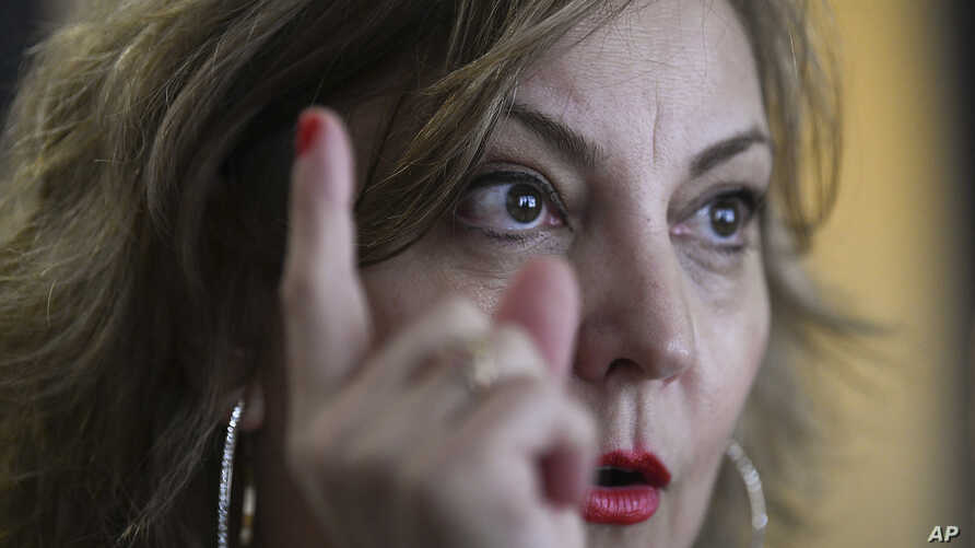 """In this Dec. 19, 2018 photo, congressional aide Claudia Guebel speaks during an interview, in Buenos Aires, Argentina. At the beginning of this year, she said, Pedro Fiorda, a senator's chief of staff, grabbed her violently by the arms like a """"hunter"""