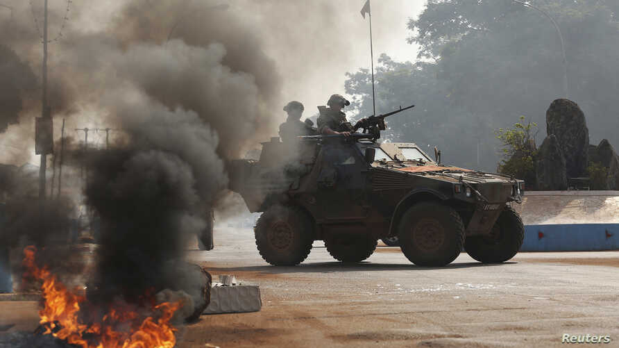 French troops secure an area after protesters from an angry mob set fire to the dead body of a Muslim man along a street in Bangui, Central African Republic, Jan. 19, 2014.