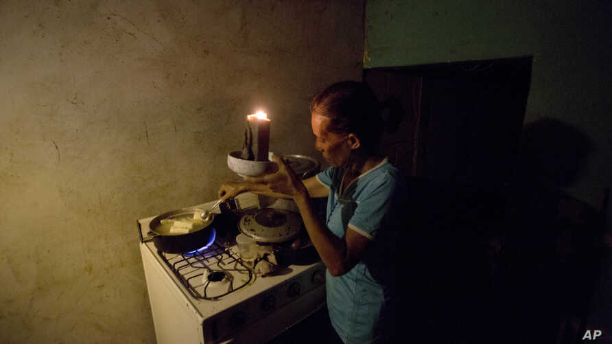 """Mireya Marquez uses candlelight to cook her dinner of boiled """"cassava,"""" also known as yuca and manioc, Aug. 19, 2018, during a blackout in Maracaibo, Venezuela. For months Maracaibo's residents have endured rolling blackouts, but things turned dire A"""