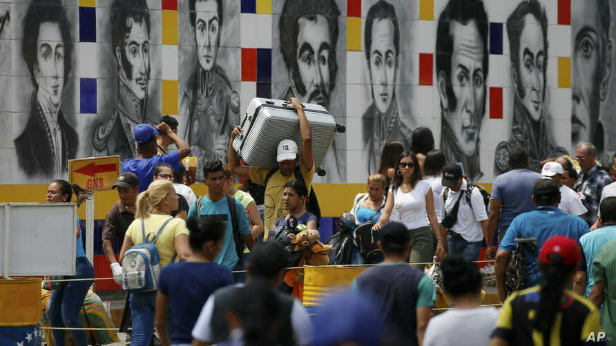 Venezuelans return to their country through the San Antonio del Tachira, Venezuela crossing, after shopping in Cucuta, Colombia, Friday, Feb. 8, 2019.